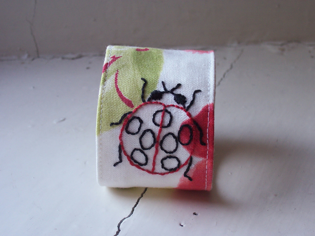 Hand embroidered textile cuff with ladybird and poppies