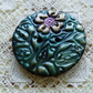 Green and gold polymer clay button