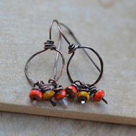 Handmade copper hoop style earrings with red and mustard Czech beads
