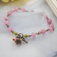 Pink bracelet with purple flower charm