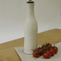 Hand thrown olive oil pourer with warm white glaze and metal spout