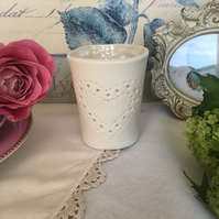 Handmade porcelain tea light holder with heart detail.