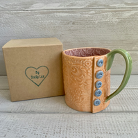 Handmade porcelain mug, rainbow mug with button detail.