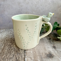 Handmade porcelain mug with bird detail.