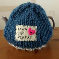 Chunky hand knitted slogan tea cosy