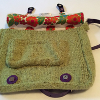 Green knitted satchel with purple leather closures and strap