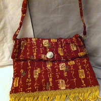 Small red chinese character print bag with gold trim