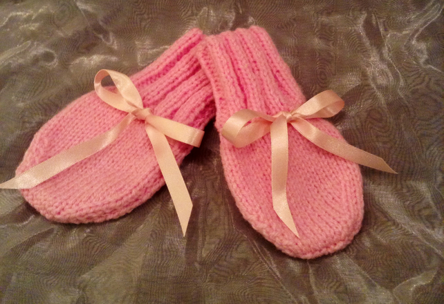 Little pink knitted baby mittens