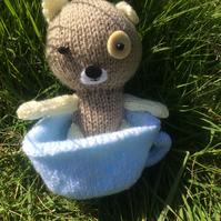 Little knitted bear in a blue tea cup
