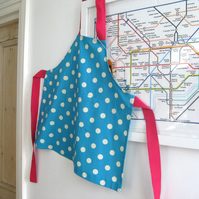 Childs apron, ages 5-7 and 8-9, spotty blue cotton with bright pink ties.