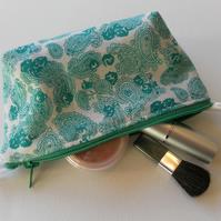 Small make up bag, green paisley pattern on a white background.