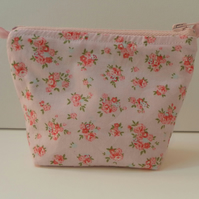 Small make up bag, red and pink roses in clusters on a pink background