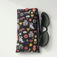 Glasses, sunglasses case, dog motifs on black background
