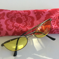 Sunglasses, glasses case, red blossom and leaves on pink background
