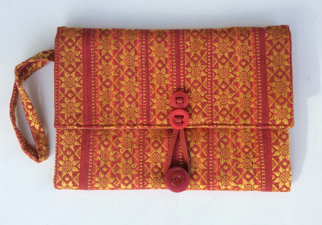 Red and gold clutch bag with wrist strap.