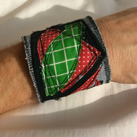 Blue denim wrist cuff, abstract appliqué pattern, red and green.