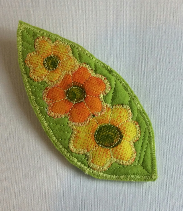 Large felt brooch, flowers on green leaf.
