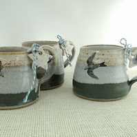Ceramic mug with swallow image glazed in moss green - misty blue - creamy white
