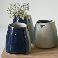 Small handmade blue and cream ceramic milk creamer pourer with bird image