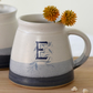 Blue and white ceramic alphabet mug illustrated with letters D and E