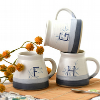 Blue and white personalised ceramic mug illustrated with letters F G H