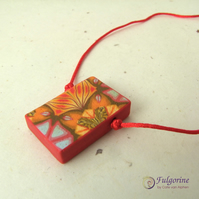 Red and orange geometric pattern polymer clay pendant on red satin cord
