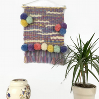Wall hanging, peg woven in a unicorn blend of merino wool with pom poms