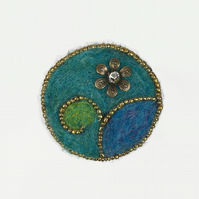 Needle felted and beaded brooch in greens and blues with flower embellishment