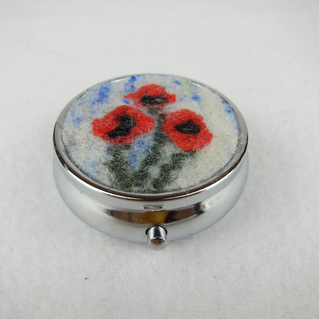 Round silver tone pill box with poppy decoration