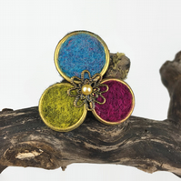Brass circle brooch with brightly coloured needle felting and a floral centre