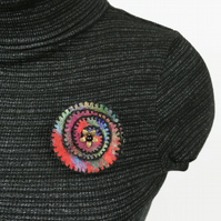 Multicoloured spiral felt brooch with black stitching