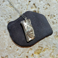 Fine silver pendant of a sea shell set on driftwood