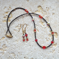Necklace & earrings in tiny black, red & gold glass beads with stars
