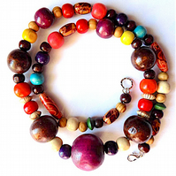 Rainbow wood bead necklace on fine chain with lobster clasp fastening.
