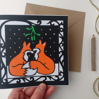 Cute Foxes Kissing Under Mistletoe In Snow - Papercut Christmas card & envelope