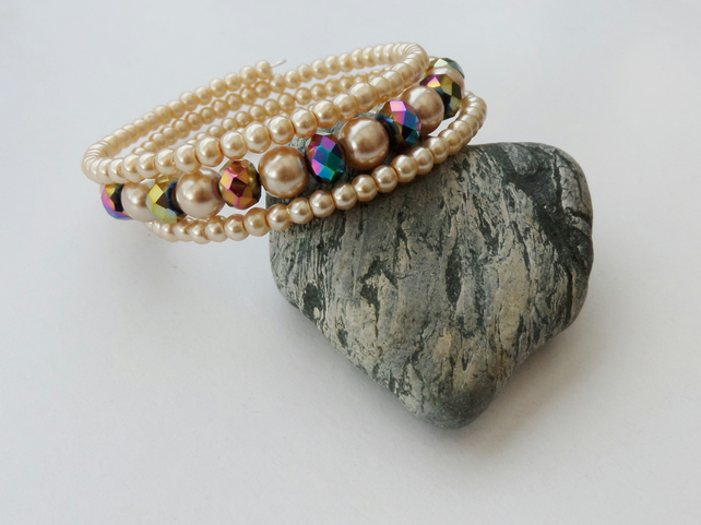 Multicoloured crystal rondelle and pale gold glass pearl memory wire bracelet.
