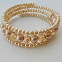 Champagne crystal rondelle and pale gold glass pearl memory wire bracelet.