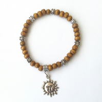 Brown wooden bracelet with Tibetan silver flower spacer beads and a sun charm