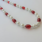White glass pearl and oval red crackle glass bead necklace.