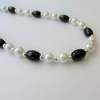 White glass pearl and oval black bead necklace.