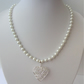 White pearl necklace with wrapped heart pendant.