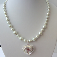 White pearl necklace with heart pendant.