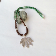 Brown, silver and green necklace with a Tibetan silver leaf pendant.