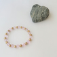 Elasticated pink crystal and bronze coloured bead bracelet