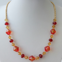 Gold and red coloured beaded necklace.