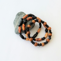 Three brown, black and patterned dyed wooden elasticated bracelets, no meatal