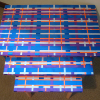 Set of 3 nest tables painted in grey, blue and peach with a weaved ribbon top