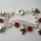 'Skulls and Roses' Charm bracelet with skull charms and red roses.