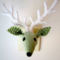 Retro green deer head trophy. Vegetarian wall hanging, antlers, hunting. Spring