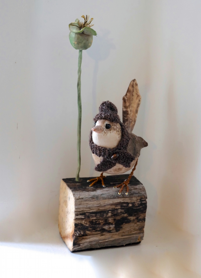Cotton wren bird on driftwood with seed pod sculpture. Hand knitted hat scarf.